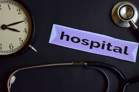Hospital on the print paper with Healthcare Concept Inspiration. alarm clock, Black stethoscope.
