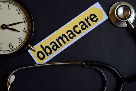 Obamacare on the print paper with Healthcare Concept Inspiration. alarm clock, Black stethoscope.