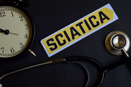 Sciatica on the print paper with Healthcare Concept Inspiration. alarm clock, Black stethoscope.