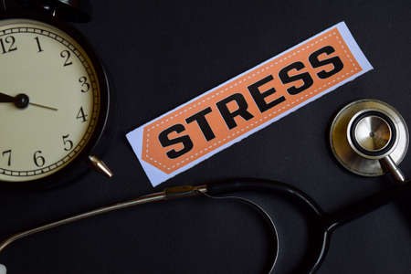 Stress on the print paper with Healthcare Concept Inspiration. alarm clock, Black stethoscope.