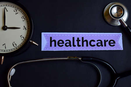 Healthcare on the print paper with Healthcare Concept Inspiration. alarm clock, Black stethoscope. 写真素材