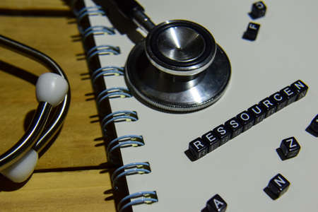 Concept retro of Ressourcen in germany on wooden cubes with stethoscope, book on wooden