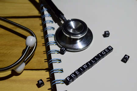 Concept retro of freiwillger on wooden cubes with stethoscope, book Stock fotó