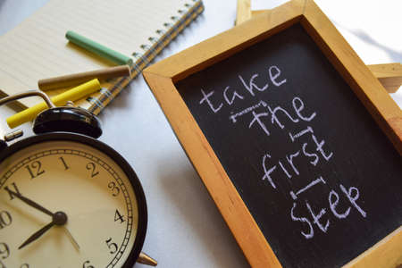 Take the first step phrase colorful handwritten on chalkboard, alarm clock with motivation and education concepts. Imagens
