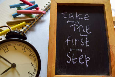 Take the first step phrase colorful handwritten on chalkboard, alarm clock with motivation and education concepts. Stock Photo