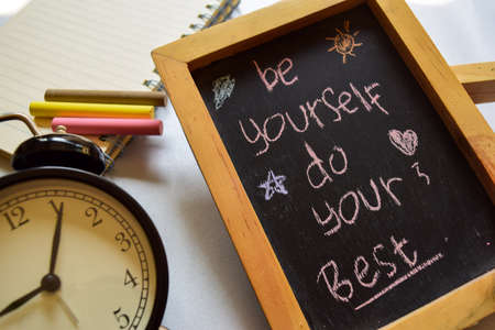 be yourself do your best on phrase colorful handwritten on chalkboard, alarm clock with motivation and education concepts. Stock Photo