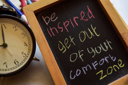 Inspírate, sal de tu zona de confort con una frase colorida escrita a mano en una pizarra, un reloj despertador con conceptos de motivación y educación. Foto de archivo