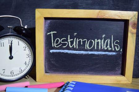 Testimonials on phrase colorful handwritten on blackboard. Education and business concept. Alarm clock, chalk, books on black background