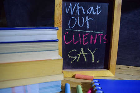 What our clients say on phrase colorful handwritten on blackboard. Education and business concept. Alarm clock, chalk, books on black background