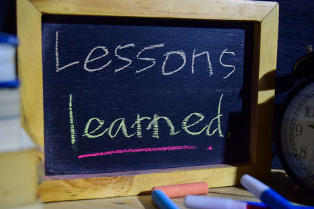 Lesson learned on phrase colorful handwritten on blackboard. Education and business concept. Alarm clock, chalk, books on black background 版權商用圖片