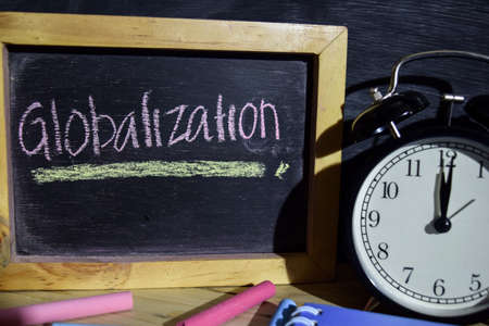 Globalization on phrase colorful handwritten on blackboard. Education and business concept. Alarm clock, chalk, books on black background 免版税图像 - 108098148