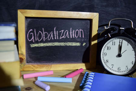 Globalization on phrase colorful handwritten on blackboard. Education and business concept. Alarm clock, chalk, books on black background