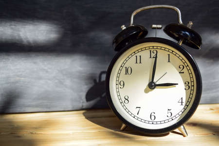 3 am/pm Back to school concept. Alarm clock on wooden with blackboard on background Stock Photo