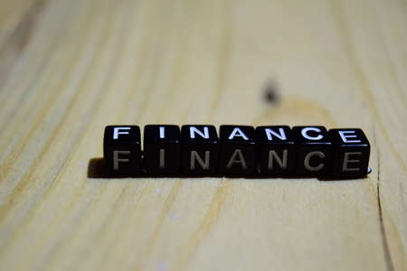 Finance written on wooden blocks. Inspiration and motivation concepts. Cross processed image on Wooden Background