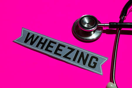 Wheezing on the paper with medicare Concept Inspiration. Stethoscope on pink bakcground Stock Photo
