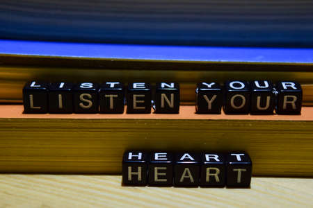 Listen your heart written on wooden blocks. Education and business concept on wooden background