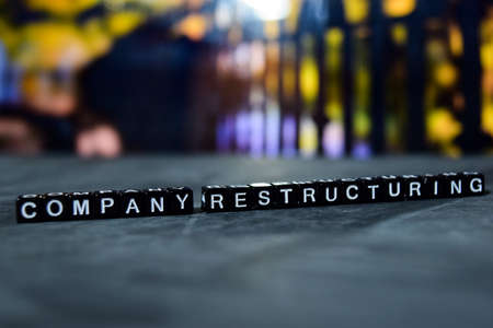 Company restructuring on wooden blocks. Business and finance concept. Cross processed image with bokeh background