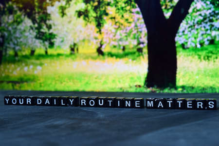 Your daily routine matters on wooden blocks. Cross processed image with bokeh background