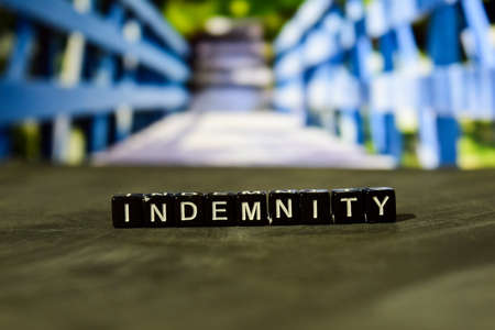 Indemnity on wooden blocks. Business and finance concept. Cross processed image with bokeh background