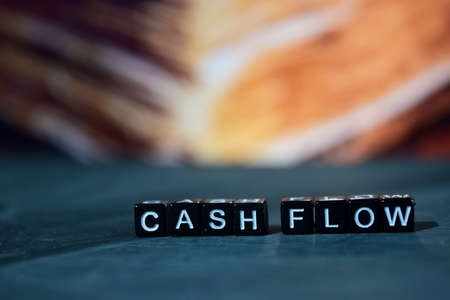 Cash flow on wooden blocks. Business and finance concept. Cross processed image with bokeh background