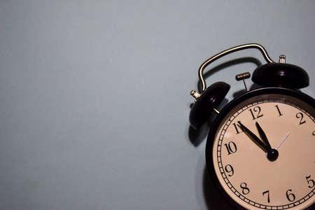 black vintage alarm clock on the grey background