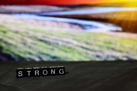 Strong on wooden blocks. Cross processed image with bokeh background