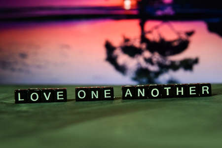 Love one another on wooden blocks. Cross processed image with bokeh background