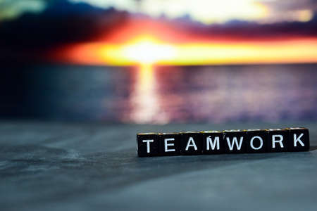 Teamwork on wooden blocks. Cross processed image with bokeh background