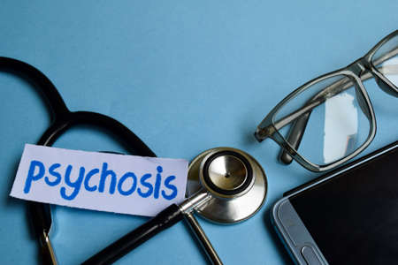 Conceptual image with Psychosis inscription with the view of stethoscope, eyeglasses and smartphone on the blue background. Medical Conceptual.