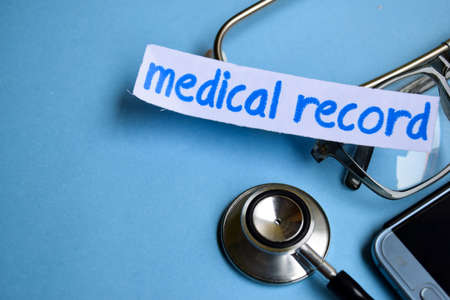 Conceptual image with Medical record inscription with the view of stethoscope, eyeglasses and smartphone on the blue background. Medical Conceptual.