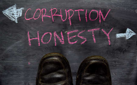 Corruption or Honesty written with color chalk concept on the blackboard Stock Photo