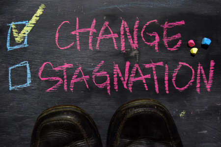 Change or Stagnation written with color chalk concept on the blackboard
