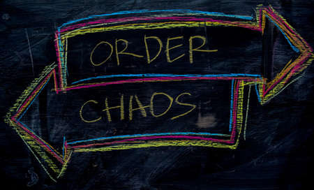 Order or Chaos written with color chalk concept on the blackboard Stock Photo