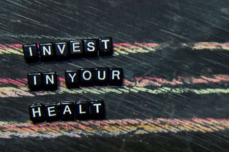 Invest in Your Health on wooden blocks. Cross processed image with blackboard background. Inspiration, education and motivation concepts with The words subject of this image is not in focus.