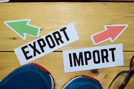 Import or Export opposite direction signs with sneaker and eyeglasses on wooden vintage background. Business, education and finance concepts