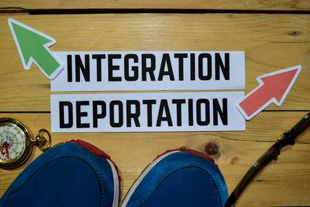Integration or Deportation opposite direction signs with sneakers, eyeglasses and compass on wooden vintage background. Business, education and finance concepts