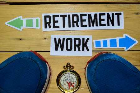 Retirement or Work opposite direction signs with sneakers and compass on wooden vintage background. Business, education and finance concepts