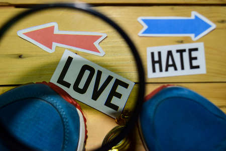 Love or Hate opposite direction signs in magnifying with sneakers and compass on wooden vintage background. Business, education and finance concepts