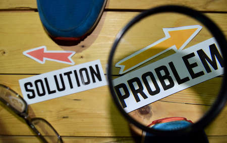 Solution or Problem opposite direction signs in magnifying with sneakers and eyeglasses on wooden vintage background. Business, education and finance concepts Фото со стока