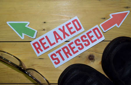 Relaxed or Stressed opposite direction signs with boots and eyeglasses on wooden vintage background. Business, education, finance and concepts
