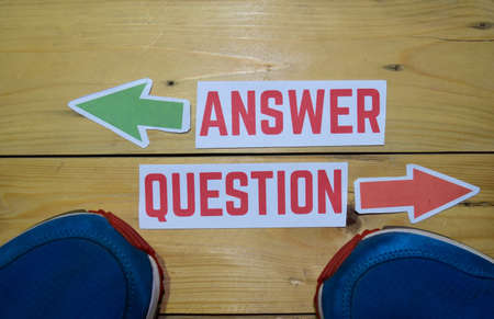 Answer or Question opposite direction signs with sneakers on wooden vintage background. Business, education, finance and concepts
