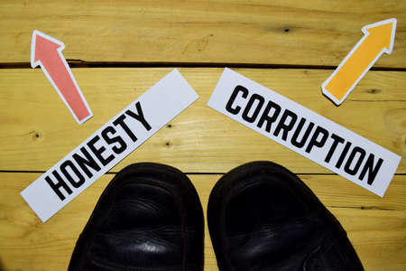 Honesty or Corruption opposite direction signs with sneakers on wooden vintage background. Business, education and finance concepts Foto de archivo
