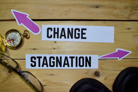 Change or Stagnation opposite direction signs with boots, eyeglasse and compass on wooden vintage background. Business and education on inspiration concepts Stock Photo