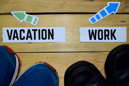 Vacation or Work opposite direction signs with sneakers and boots on wooden vintage background. Business and education concepts