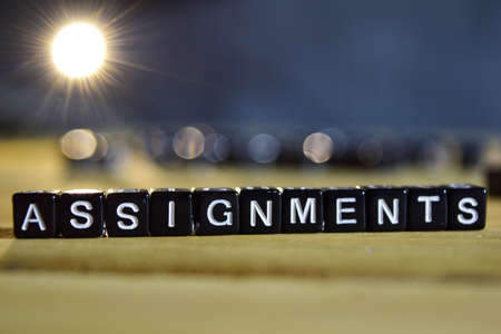 ASSIGNMENTS concept wooden blocks on the table. With personal development and motivation concept on blurred or black background Reklamní fotografie