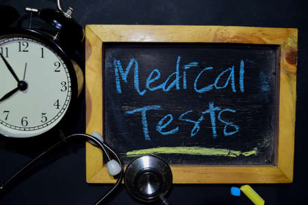 The words Medical Tests handwriting on chalkboard on top view. Alarm clock, stethoscope on black background. With education, medical and health concepts