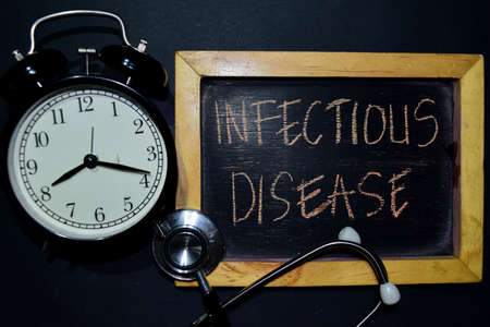 The words Infectious Disease handwriting on chalkboard on top view. Alarm clock, stethoscope on black background. With education, medical and health concepts Stock Photo