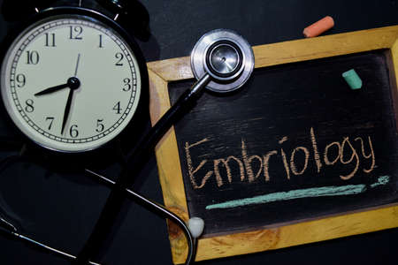 The words Embriology handwriting on chalkboard on top view. Alarm clock, stethoscope on black background. With education, medical and health concepts