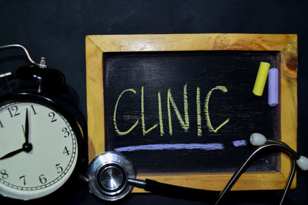 The words Clinic handwriting on chalkboard on top view. Alarm clock, stethoscope on black background. With education, medical and health concepts Фото со стока