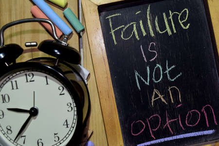 Failure Is Not An Option on phrase colorful handwritten on chalkboard and alarm clock with motivation, inspiration and education concepts. Table background
